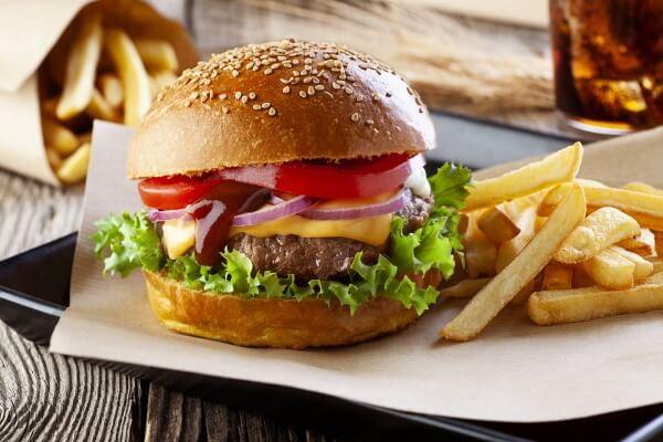 Hamburger classico con papatine fritte su vassoio nero